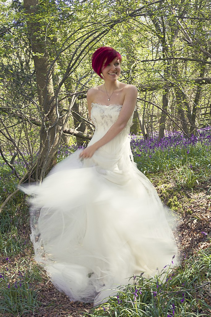 Girl in wedding dress with movement and bluebells in the background
