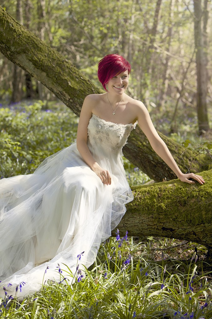 bridal wedding portrait sitting on a fallen tree with bluebells photographed by Joseph Tufo and edited by Emy Lou