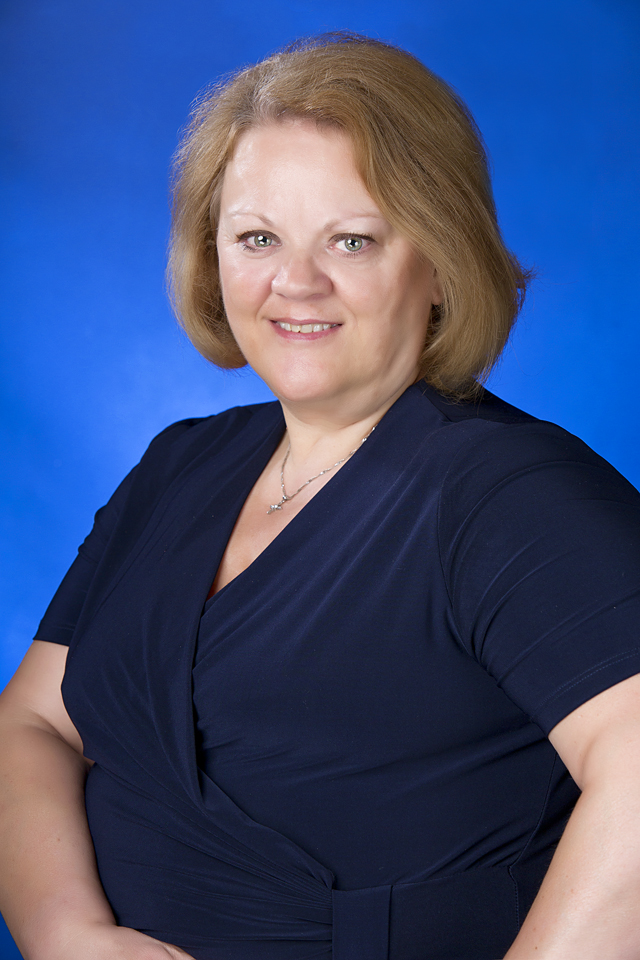 business headshot of a women with a blue background